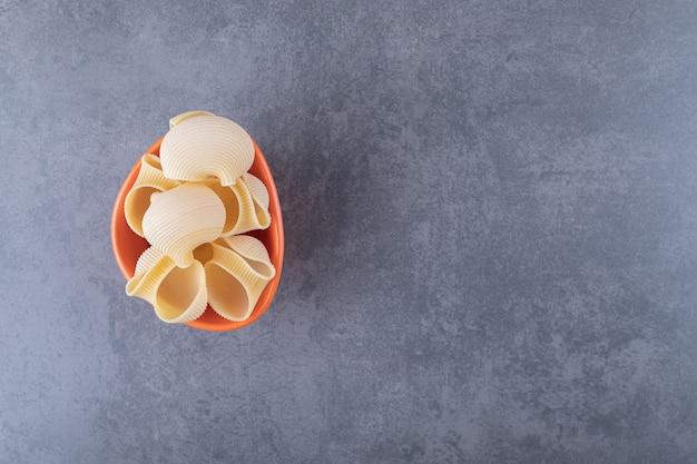 Bündel rohe muschelnudeln in orangefarbener schüssel.