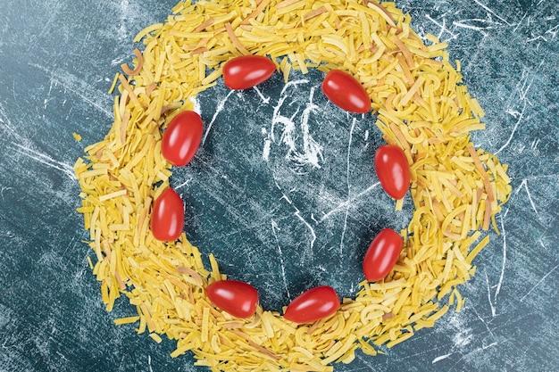Bündel rohe nudeln auf blauem hintergrund mit tomaten. hochwertiges foto
