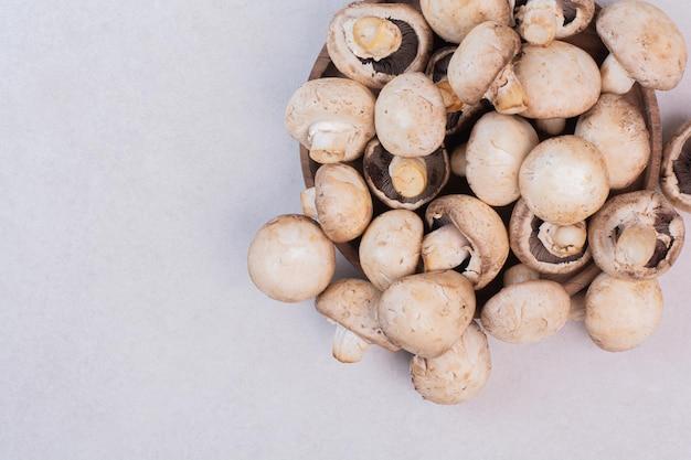 Bündel rohe pilze auf weißer oberfläche.