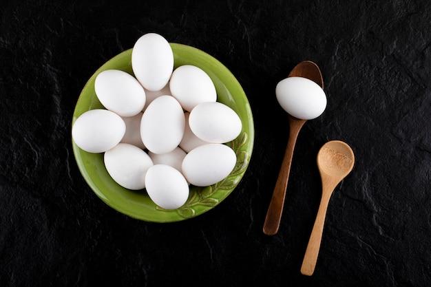 Bündel roher eier auf grünem teller mit holzlöffeln.