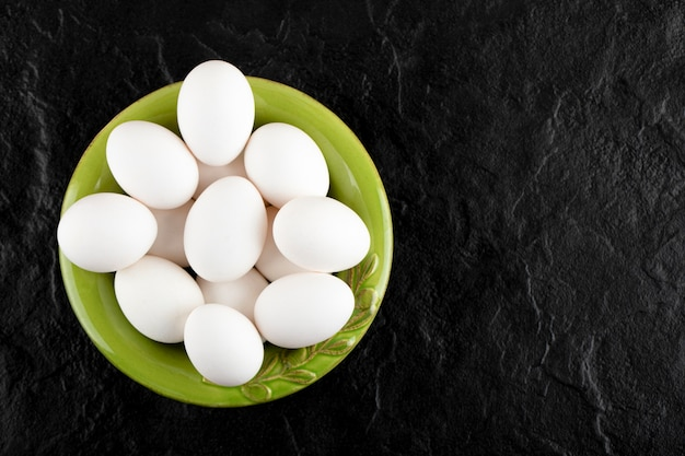 Bündel roher eier auf grünem teller.