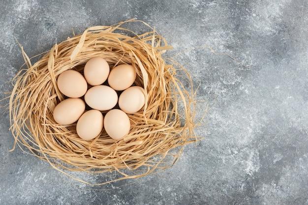 Bündel roher eier mit vogelnest auf marmoroberfläche.