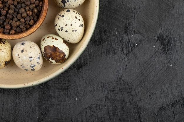Bündel roher eier und schüssel pfefferkörner auf pfanne.