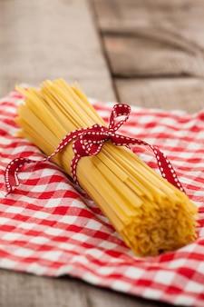 Bündel roher spaghetti mit rotem band auf serviette gebunden