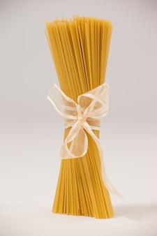 Bündel roher spaghetti mit weißem band auf serviette gebunden