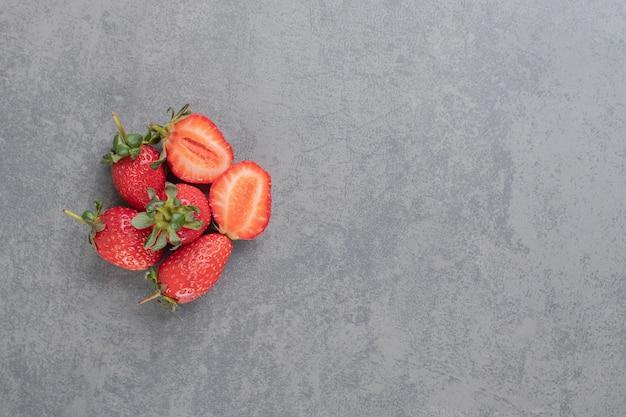 Bündel rote erdbeeren auf marmorhintergrund. foto in hoher qualität