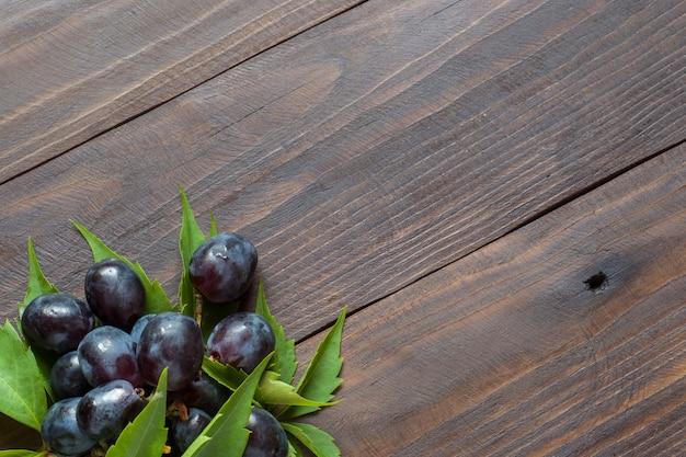 Bündel rote trauben auf dem hintergrund eines holztischs mit einer kopie des raumes