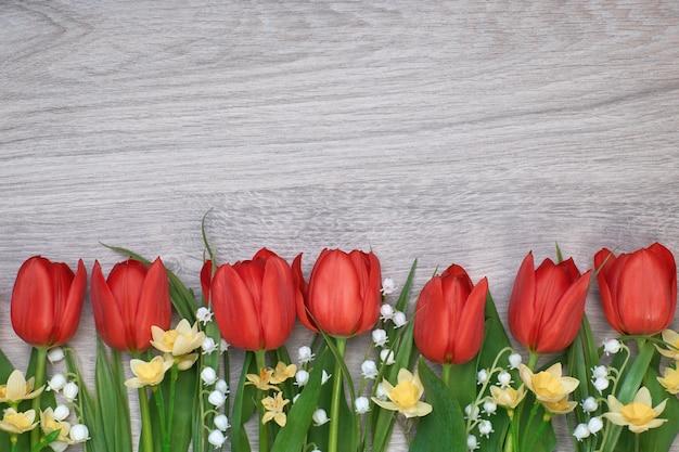 Bündel rote tulpen, narzissen und maiglöckchen blüht auf hellem hölzernem hintergrund