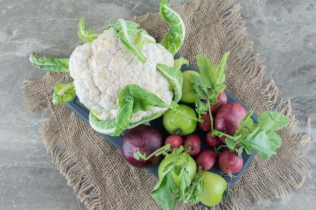 Bündel rote zwiebeln, blumenkohl, grüne tomaten, rüben und rübenblätter auf einer schwarzen platte auf marmor.