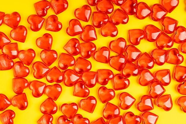 Bündel roter herzform süßer bonbons, die auf leuchtendem leuchtendem gelb liegen