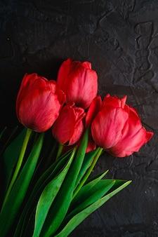 Bündel roter tulpenblumen auf strukturiertem schwarzem hintergrund, kopierraum der draufsicht