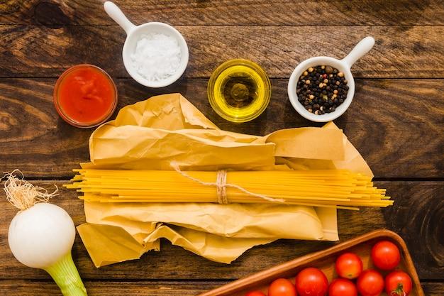 Bündel spaghettis nahe gewürzen und gemüse