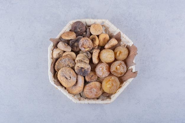 Bündel süßer getrockneter feigen in weidenkorb gelegt.