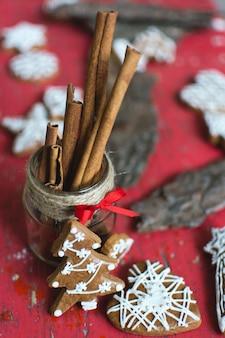 Bündel traditioneller weihnachtslebkuchen mit zuckerglasur auf einem roten hölzernen hintergrund