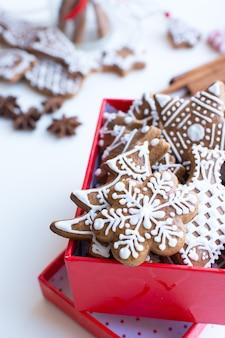 Bündel traditioneller weihnachtslebkuchen mit zuckerglasur in einem roten papierkasten