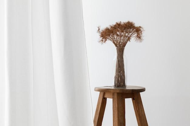 Bündel trockener papyruspflanze in einer glasvase auf einem hölzernen hocker durch einen weißen vorhang