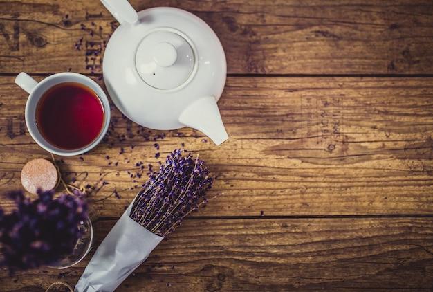 Bündel trockener schnittlavendel, tasse tee und teekanne auf holztisch. ansicht von oben.