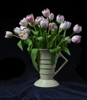 Bündel tulpen in einer art-deco-vase mit schwarzem hintergrund