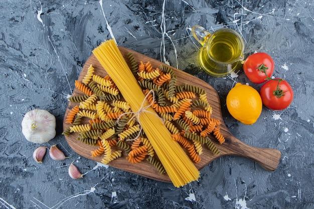 Bündel ungekochte spaghetti in einem seil mit bunten nudeln und gemüse.