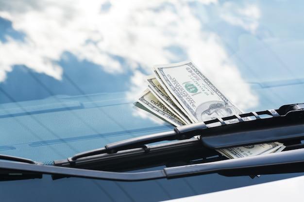 Bündel us-dollar-banknoten auf einem auto unter dem autowischer auf einer windschutzscheibe