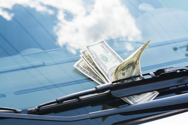 Bündel us-dollar banknoten verließ auf einem auto unter dem autowischer auf einer windschutzscheibe