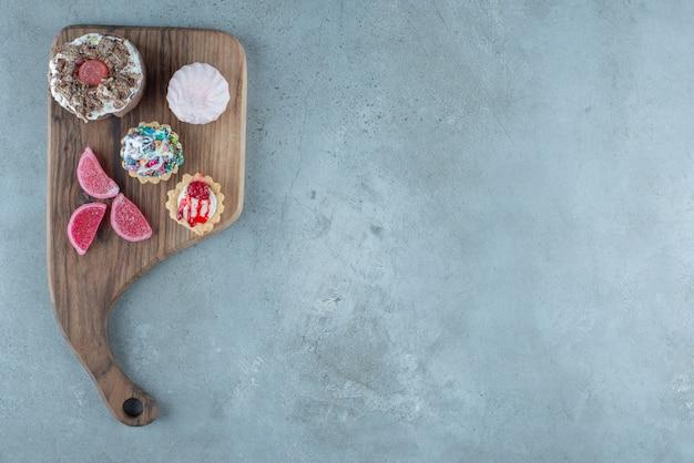 Bündel verschiedener backwaren und marmeladen auf einem holzbrett auf marmorhintergrund. hochwertiges foto