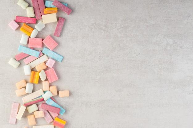 Bündel verschiedener kaugummis auf steintisch gelegt.