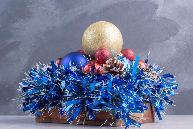 Bündel verschiedener weihnachtsdekorationen auf einem holzbrett auf marmoroberfläche
