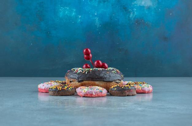 Bündel von donuts verziert mit einer weihnachtsbeerenverzierung auf marmor.