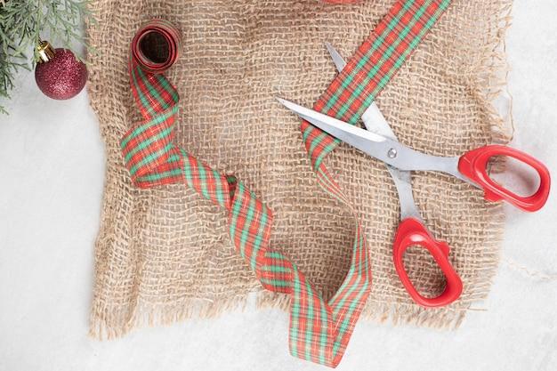Bündel weihnachtsdekorationen mit schere auf sackleinen