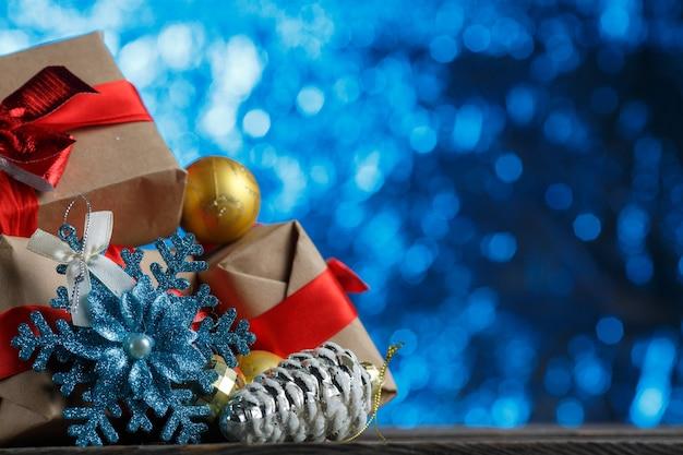 Bündel weihnachtsgeschenk und dekoration nahaufnahme. goldene kugel, silberner tannenzapfen und glänzende schneeflocke. silvestergeschenk in papier mit schleife eingewickelt. feiertagszubehör auf lametta verschwommenem hintergrund