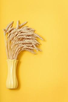 Bündel weizenähren in gelber vase auf papier