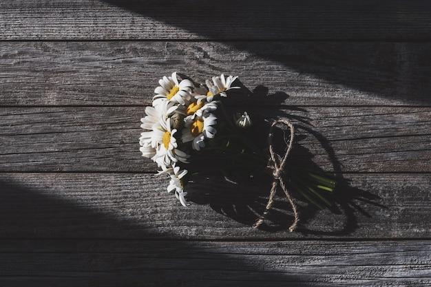 Bündel wildblumen auf hölzernem hintergrund