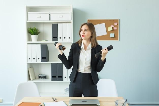 Büro-, fitness- und personenkonzept - geschäftsfrau, die in ihrem büro arbeitet und sport treibt