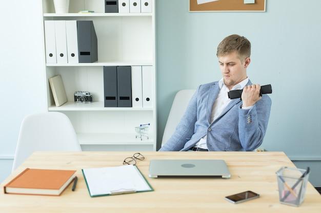 Büro-, fitness- und personenkonzept - geschäftsmann, der in ihrem büro arbeitet und sport treibt