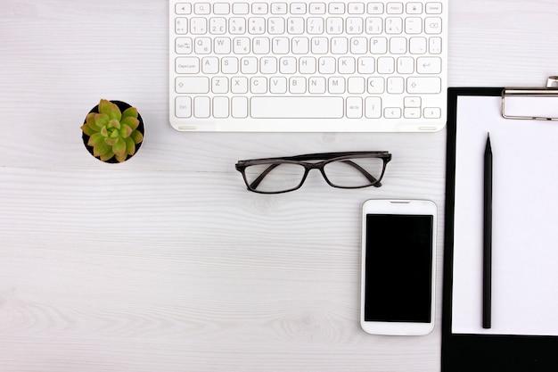 Büro-flatlay mit weißer tastatur, lesebrille, haustier und notizbuch