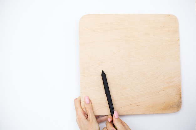 Büro-frauen-hände, die ein baum-brett auf weißem hintergrund halten. exemplar. platz für text