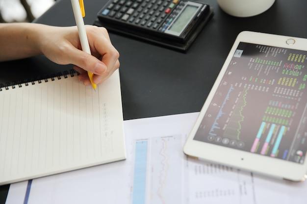 Büro-frauenhand, die an den geschäftspapieren und der tablette arbeitet