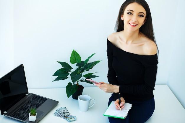 Büro-geschäftsfrau, die auf dem tisch lächelt und sitzt.