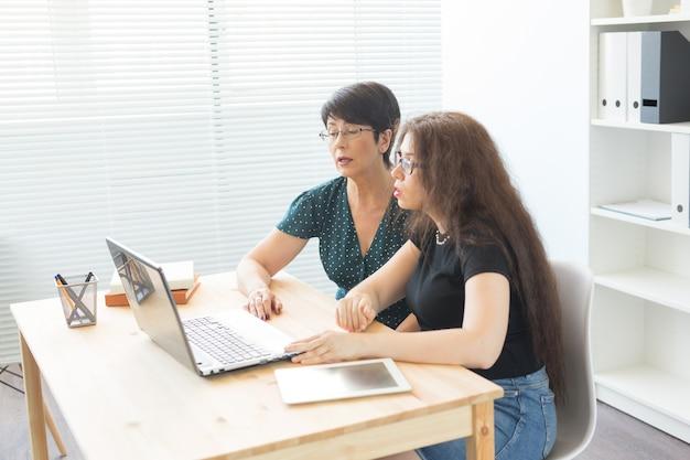 Büro-, geschäftsmann- und grafikdesignerkonzept - frauen sitzen und diskutieren ideen im