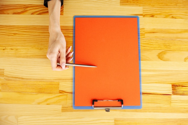 Büro-hand, die einen ordner mit einem rote farbpapier und -stift auf dem hintergrund des holztischs hält.
