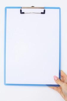Büro-hand, die einen ordner mit einem weißen farbpapier auf dem hintergrund der weißen tabelle hält