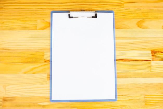 Büro-hand, die einen ordner mit einem weißen farbpapier auf dem hintergrund des holztischs hält.
