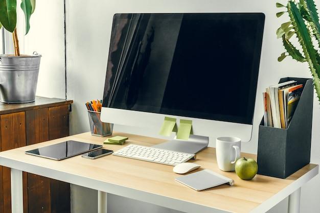 Büro- oder ausgangsarbeitsplatz, computermonitor mit schwarzem bildschirm auf bürotisch mit versorgungen
