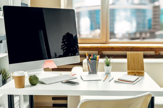 Büro- oder heimarbeitsplatz. computermonitor mit schwarzem bildschirm auf bürotisch mit versorgungen
