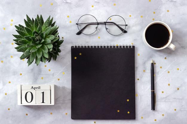 Büro- oder stammtischkalender 1. april. notizblock, kaffee, saftig, gläser auf marmorhintergrund
