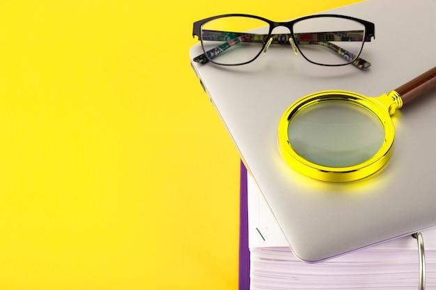 Büro, ordner mit dokumenten, die auf überprüfung warten, lupe, auf einem gelb