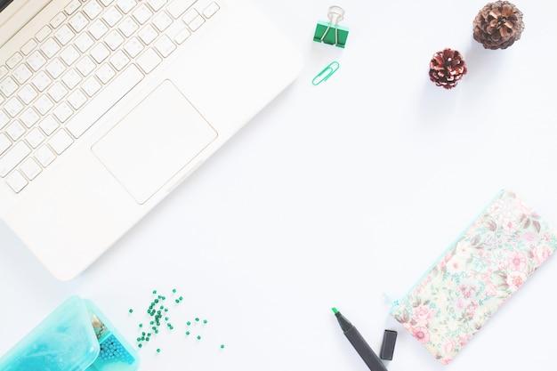 Büro schreibtisch tisch mit laptop, lieferungen, tannenzapfen, stift, glasperlen. draufsicht mit kopie raum