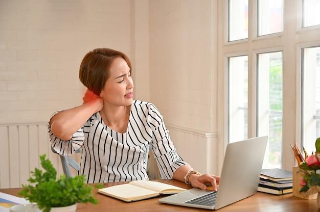 Büro-syndrom, frau, die steifen hals massierend berührt, um die schmerz in den muskeln zu entlasten, die in der falschen falschen lage arbeiten.