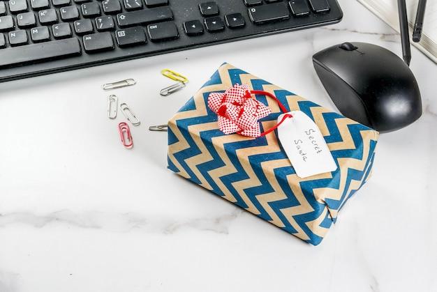Büro-weihnachtsfeierkonzept, die idee des teilens des geschenkgeheimnisses sankt. tastatur, maus, notizbuch,